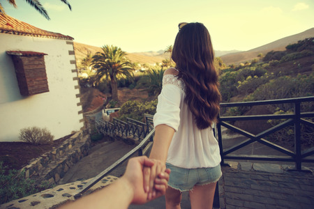 lead: Beautiful girl holding mans hand and leading him. Love and travel concept. Beautiful tropical landscape. Stock Photo