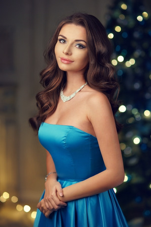 Portrait of young beautiful pretty woman wearing elegant fashionable evening dress and posing in christmas decorated interior against defocused bokeh background