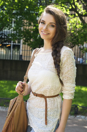 Outdoor summer portrait of young beautiful girl with stylish braid wearing fashionable white lace dress Foto de archivo
