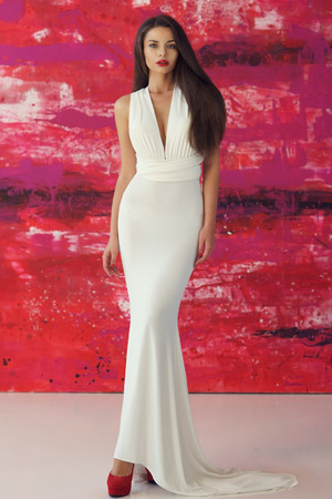 Young beautiful stunning woman posing in long elegant white evening dress and red shoes against stylish red background 스톡 콘텐츠