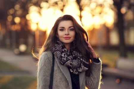 Hermosa chica con estilo joven con el pelo largo y oscuro caminar al aire libre en capa gris en la puesta del sol. Retrato del primer con la luz hermosa puesta de sol Foto de archivo - 55591700