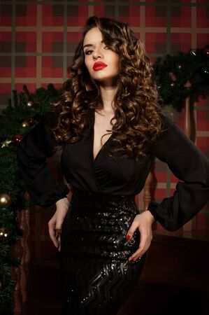 glamour hair: Young beautiful woman posing in elegant black evening dress in christmas interior. Stock Photo