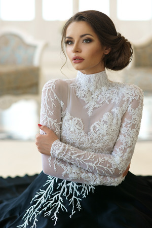 Closeup portrait of young beautiful girl in evening dress and with hairdress sitting on floor in white luxury interiors Stock Photo