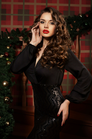 glamour hair: Young beautiful woman posing in elegant black evening dress in christmas interior