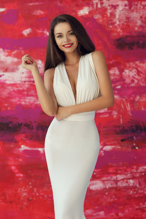decolette: Portrait of young beautiful smiling girl wearing white evening dress with decolette, posing against stylish red background Stock Photo