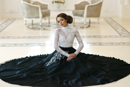 Beautiful elegant girl in expensive evening dress sitting on floor in luxury white interior Stock Photo