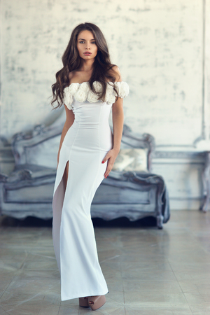 Young beautiful lady in white evening dress posing in luxury interior, standing