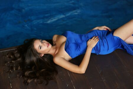 vogue style: Fashion vogue style portrait of young beautiful stylish lady lying on wooden floor. Sexy pretty woman in elegant evening blue dress