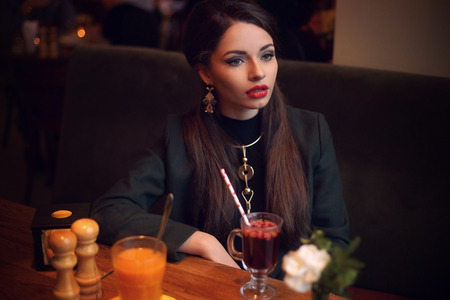 Young beautiful pretty stylish dressed formal woman looking away and drinking mulled wine Stock Photo