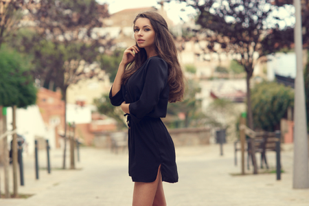 gorgeous: Young beautiful stylish girl in black summer dress walking and posing between trees at alley