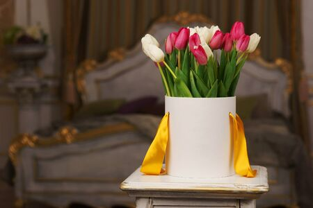 flower box: White flower box with white and pink tulips standing in luxury interior. Shallow dof Stock Photo