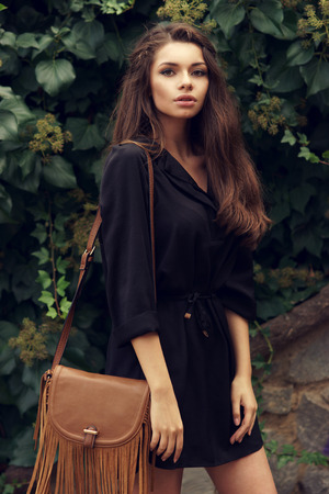 Young beautiful and pretty stylish girl standiing against wall of green leafs. Fashionable woman in black summer dress with brown handbag looking at you.