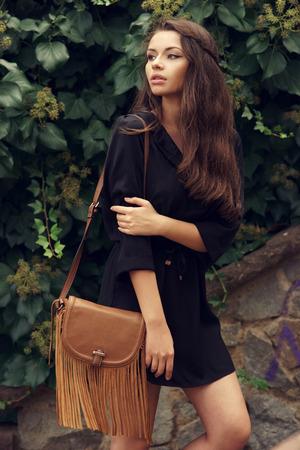 Stylish beautiful young girl walking outdoors near green leafs. Trendy woman in black dress with brown handbag looking away