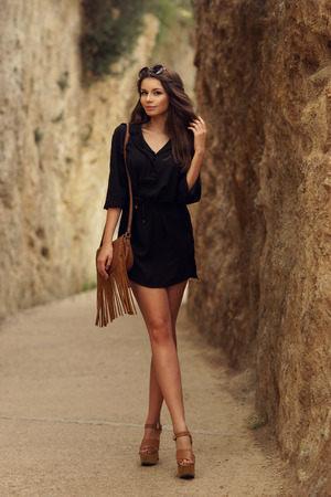 Beautiful stylish girl wearing black dress and sunglasses with long sexy legs walking on a path at nature between rocks