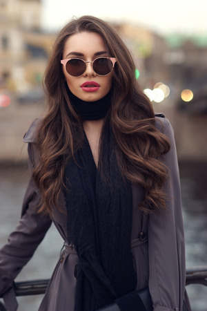 Fashionable glamorous girl with long curly hair wearing black dress, scarf, gray classy coat and sunglasses posing at city streets and looking at you or in camera. Fashion vogue style outdoor portrait Stockfoto