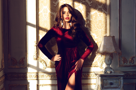 Fashion vogue style portrait of young stunning woman posing in red dress in sunset lightning with shados in interior. Gorfeous glamourous woman with dark long curly hair