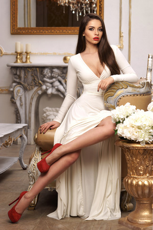 Vogue fashion style portrait of young beautiful pretty elegant rich woman wearing evening dress and sitting on armchair in luxury apartments