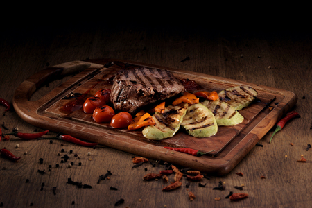 vegetable marrow: Grilled marble beef steak with roasted vegetables: sliced vegetable marrow, bell pepper and cherry tomatoes on wooden board on rustic wooden counter Stock Photo