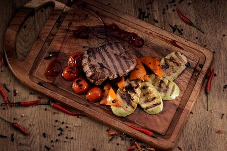 vegetable marrow: Overhead view of grilled marble beef steak with roasted vegetables: sliced vegetable marrow, bell pepper and cherry tomatoes on wooden board on rustic wooden counter