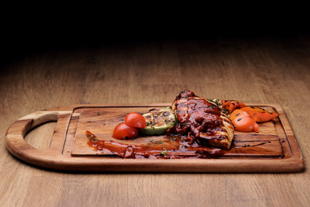 vegetable marrow: Grilled chicken fillet with roasted vegetables: sliced vegetable marrow, bell pepper and fresh cherry tomatoes with red sauce on wooden board on rustic wooden counter