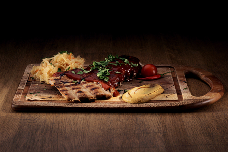 red braised: Port steak with red sauce with braised cabbage, fresh cherry tometoes and mustard served on wooden board on rustic wooden counter