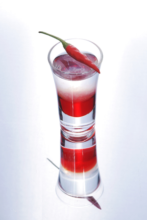 shooters: Colorful layered shot with reflection. Alcohol red shooter with chili pepper