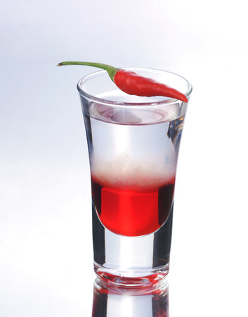 shooter drink: Colorful layered shot with reflection. Alcohol red shooter with chili pepper