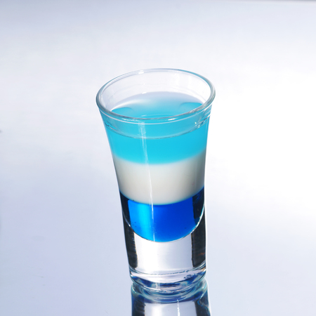 shooters: Colorful layered shot isolated on white gray gradient background with reflection. Alcohol shooter Stock Photo