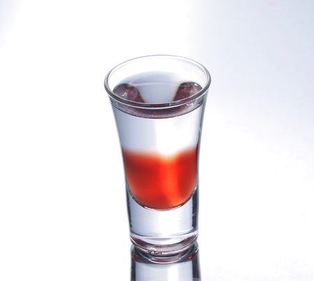 shooter drink: Colorful layered shot isolated on white gray gradient background with reflection. Alcohol shooter Stock Photo
