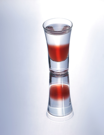 gray gradient reflection: Colorful layered shot isolated on white gray gradient background with reflection. Alcohol shooter Stock Photo