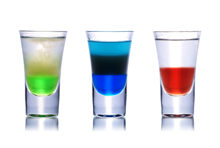 Set of colorful alcoholic cocktails in shot glasses isolated on white with reflection. Stock Photo