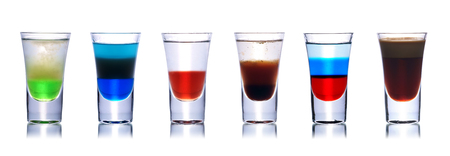 shooter drink: Set of colorful alcoholic cocktails in shot glasses isolated on white with reflection. Stock Photo