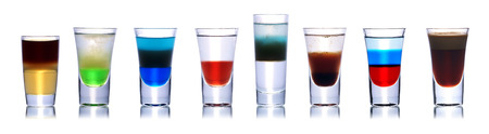 shooters: Set of colorful alcoholic cocktails in shot glasses isolated on white with reflection. Stock Photo