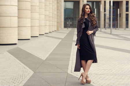 pretty brunette woman: Pretty beautiful business woman in elegant black dress and gray coat against city background.