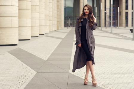 Mujer de negocios muy hermosa en elegante vestido negro y abrigo gris sobre fondo de ciudad. Foto de archivo