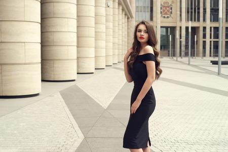 Donna abbastanza bella di affari in vestito nero elegante contro la priorità bassa della città.