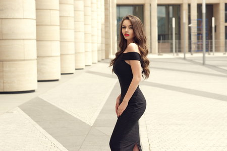 Pretty beautiful business woman in elegant black dress against city background.