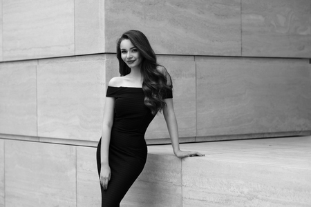 strret: Black and white portrait of young beautiful elegant woman in black dress. Pretty sensual girl with long curly hair posing outdoors at city street Stock Photo