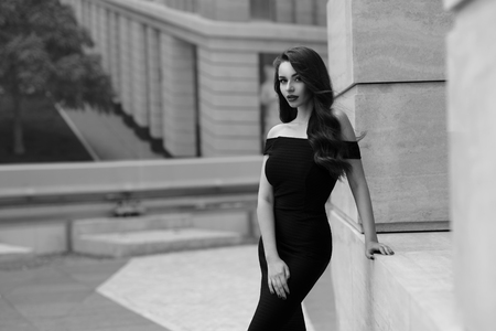 Black and white portrait of young beautiful elegant woman in black dress posing outdoors at city street