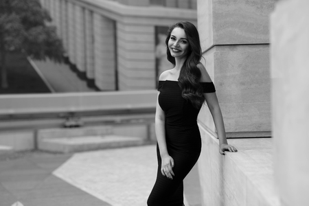 strret: Black and white portrait of young beautiful elegant woman in black dress posing outdoors at city street