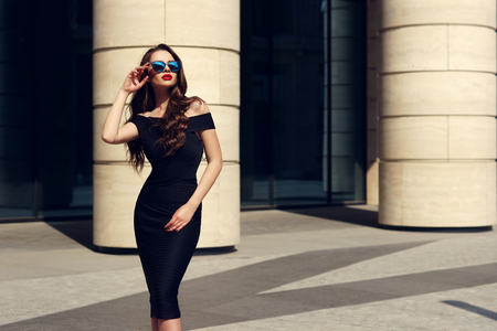the look: Young beautiful stylish girl posing at summer city streets on a sunny day wearing black dress and sunglasses.