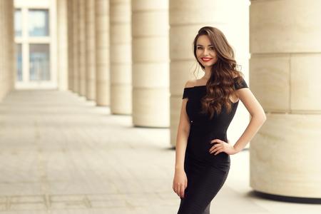 belle femme en robe noire élégante sur fond de ville.