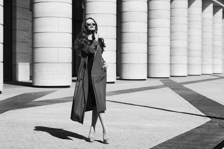 high day: Fashion vogue style dynamic portrait of young beautiful pretty woman posing at city street in black dress, gray coat and sunglasses.