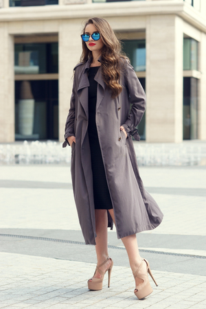 windy day: Outdoor dynamic fashion portrait of young beautiful stylish woman in black dress, grey coat and sunglasses walking on a windy day against city background Stock Photo