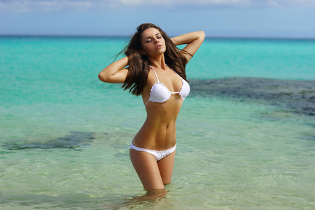 ocean water: Pretty beautiful woman in white swimwear bikini posing in blue sea water Stock Photo