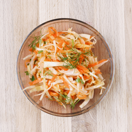 carat: Carat and coleslaw salad in a glass bowl on rustic wooden table. Top view