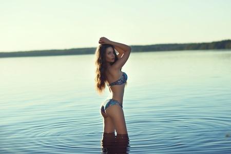 Stunning beautiful girl posing in blue bikini in the lake.