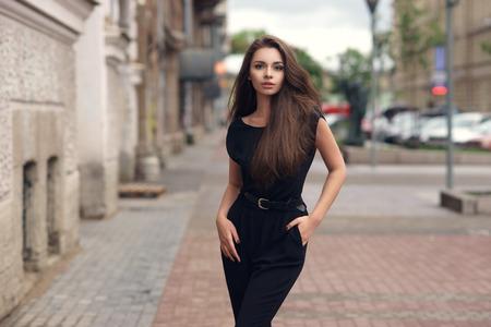 패션 스타일 초상화 바람이 부는 날에 도시 거리에서 산책하는 검은 드레스에 젊은 아름 다운 우아한 여자.