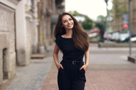 Fashion style portrait of young happy smiling beautiful elegant woman in black dress walking at city streets. 스톡 콘텐츠