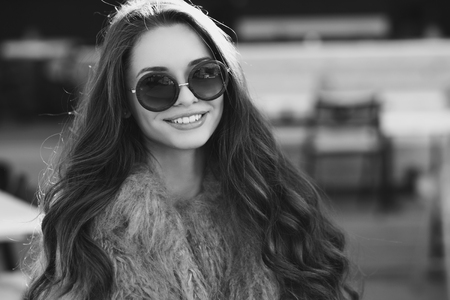 blackwhite: Trendy drssed fashionable girl wearing fur coat. Young pretty beautiful woman with long curly hair looking at you.